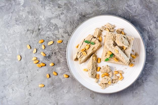 Кусочки подсолнечника и арахисовой халвы и листья мяты на тарелке и орехи рядом на столе. калорийное восточное лакомство. вид сверху.