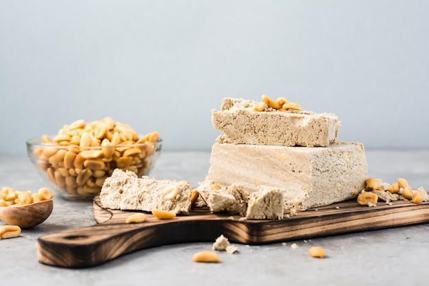 テーブルのまな板にひまわりとピーナッツのハルヴァのかけら。カロリーオリエンタルデザート