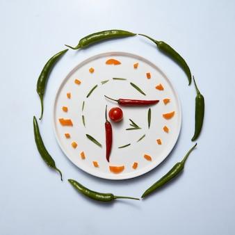 Кусочки сладкого перца, зеленого перца чили, веточки розмарина и помидора на белой тарелке в современной композиции в виде часов на белом фоне. вид сверху