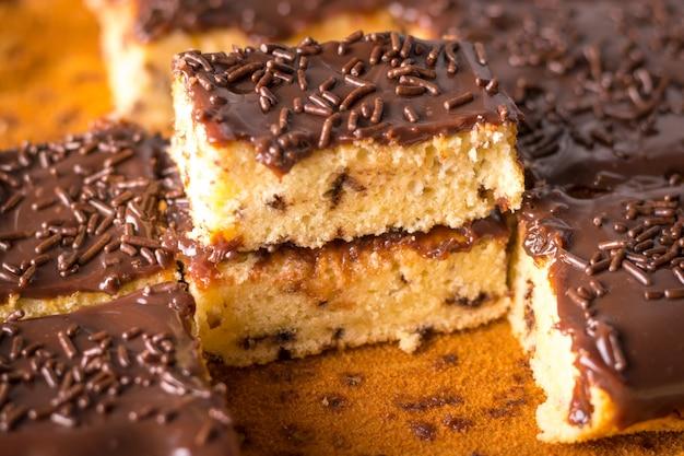 ミルクチョコレートのフロスティングとブリガデイロをベーキングペーパーに振りかけるチクチクするケーキのかけら