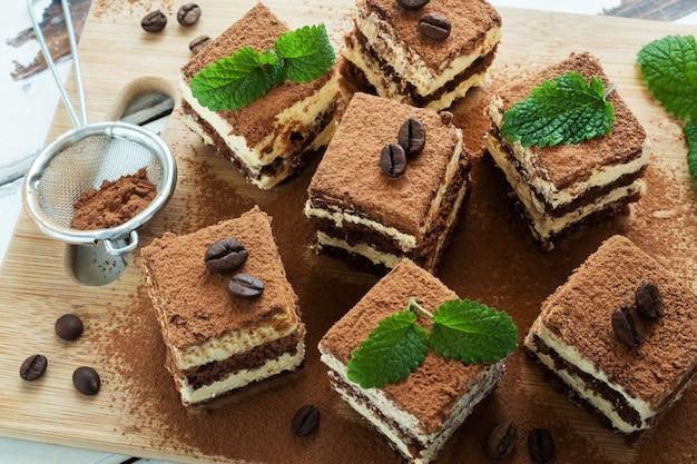 Кусочки тирамису с нежными сливками, кофейными зернами и листьями мяты.