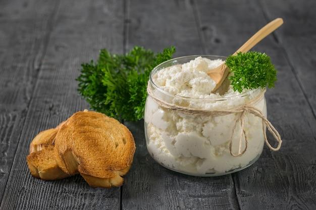 구운 빵 조각과 나무 테이블에 신선한 코티지 치즈 유리 항아리. 건강한 식단의 개념.