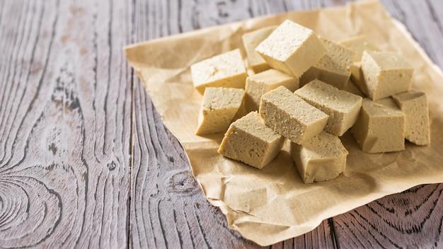 Кусочки сыра тофу на листе бумаги на деревянном столе. соевый сыр. вегетарианский продукт.