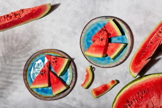 접시에 있는 수박 조각과 손바닥의 그림자와 트렌디한 햇빛이 있는 회색 배경 사진