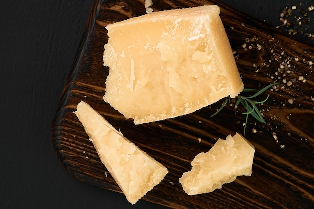 Pieces of parmigiano cheese on a cutting board. top view of hard cheese on a dark background.