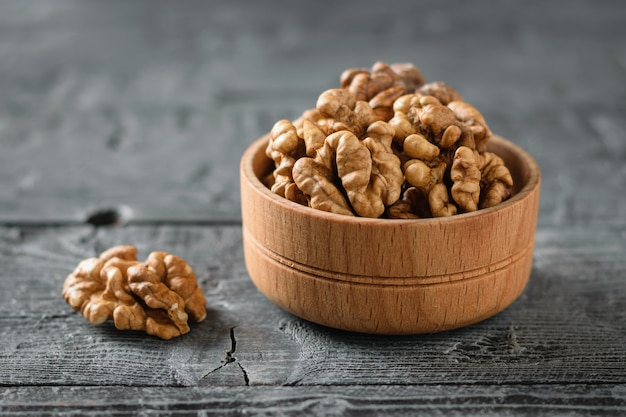 Pieces of peeled walnut in a wooden bowl on a dark wooden table.