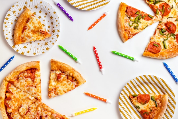 Pieces of pizza and colored candles for a cake on a white surface. birthday with junk food. children's party. top view with copy space for text. flat lay