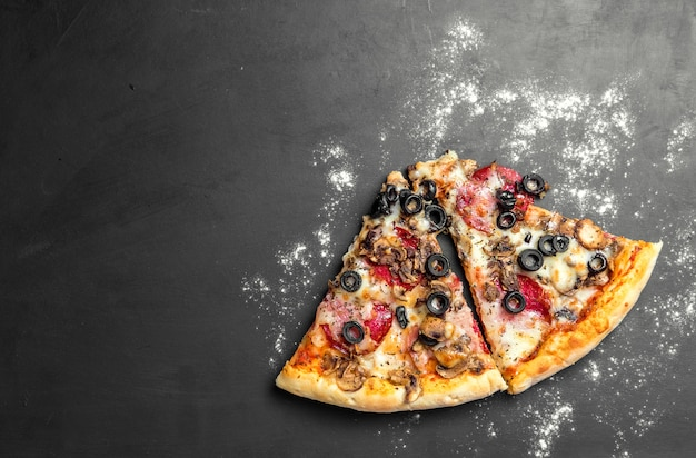 Pieces of pizza on dark black wooden board, traditional italian pizza