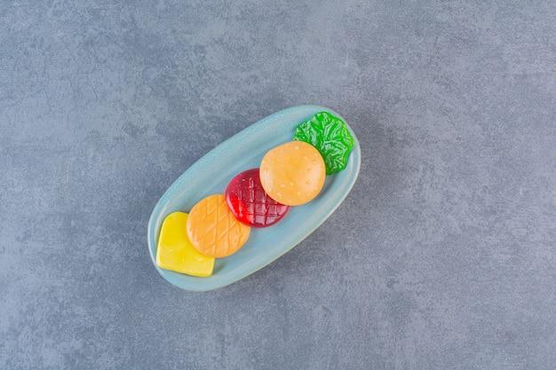 Pezzi di hamburger di plastica sul piatto, sulla superficie di marmo