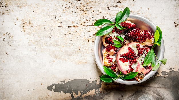 Pieces pomegranate with leaves in a cup top view. on rustic background. free space for text . top view