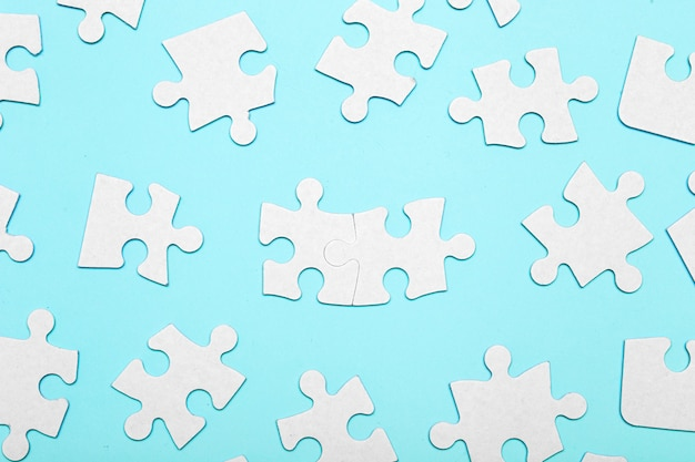 Pieces of a puzzle connected on a blue background with many other pieces of the puzzle. business teamwork concept