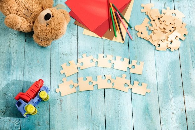 Pieces of puzzle, crayons, toy truck, teddy bear and paper on a wooden table. concept of childhood and education.