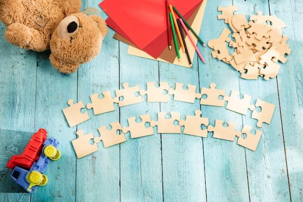 Pezzi di puzzle sulla superficie del tavolo in legno con giocattoli e colori