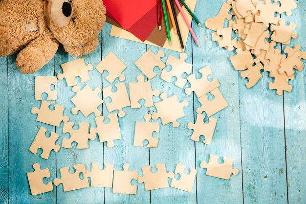 Pieces of puzzles on the surface of wooden table with toys and colors