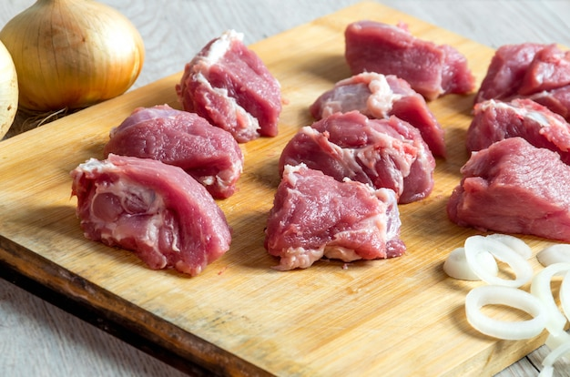 Pieces of raw beef and onion rings on cutting boar