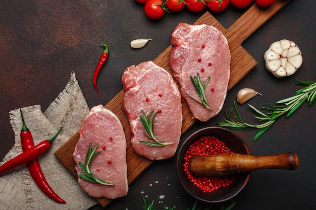 Pieces of raw pork steak on cutting board with cherry tomatoes, rosemary, garlic, pepper, salt and spice mortar on rusty brown background