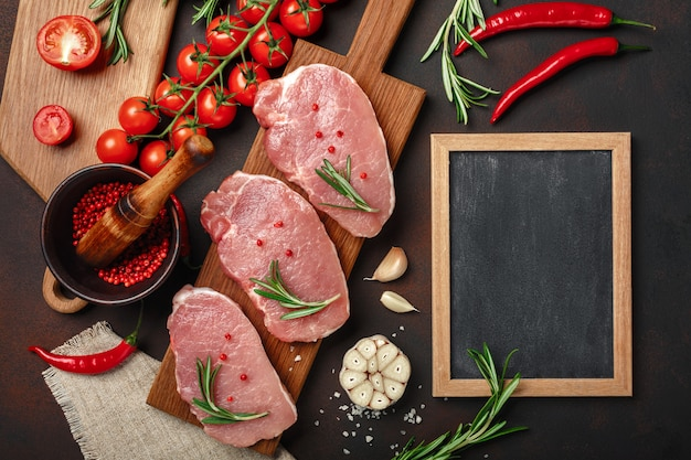 Pieces of raw pork steak on cutting board with cherry tomatoes, rosemary, garlic, pepper, salt and spice mortar