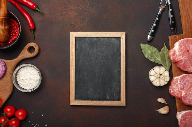 Pieces of raw pork steak on cutting board with cherry tomatoes, rosemary, garlic, red pepper, bay leaf, onion, mortar and chalk board on rusty brown background