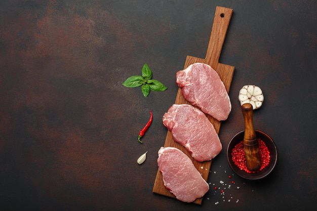 Pieces of raw pork steak with basil, garlic, pepper, salt and spice mortar on cutting board and rusty brown background with space for your text