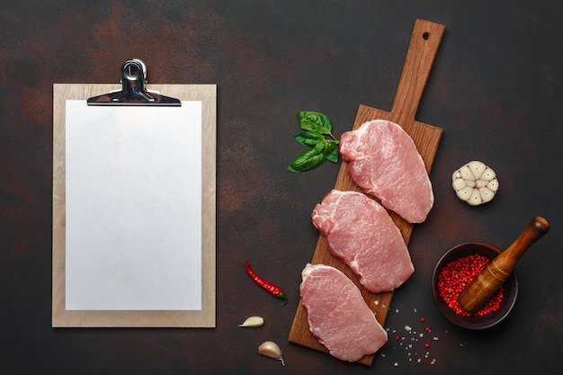 Pieces of raw pork steak with basil, garlic, pepper, salt and spice mortar and tablet on cutting board and rusty brown background with space for your text.