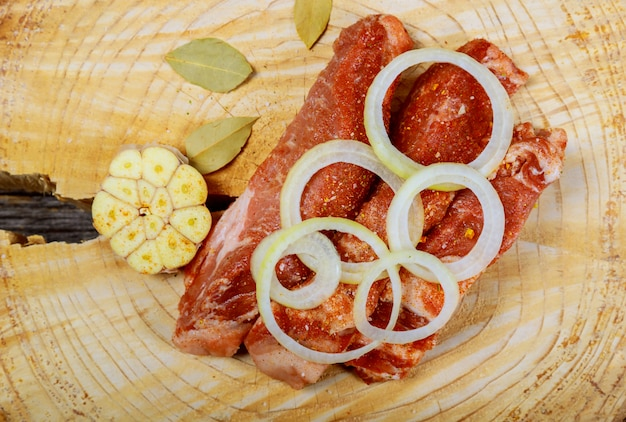 Pieces of raw pork steak with spices and herbs with garlic and onions, salt and pepper