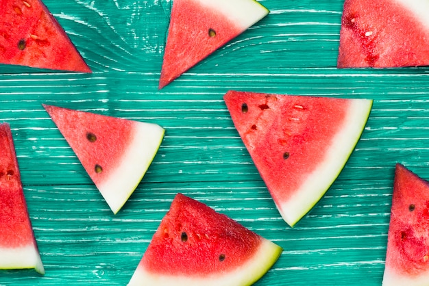 Pieces of red watermelon on green background