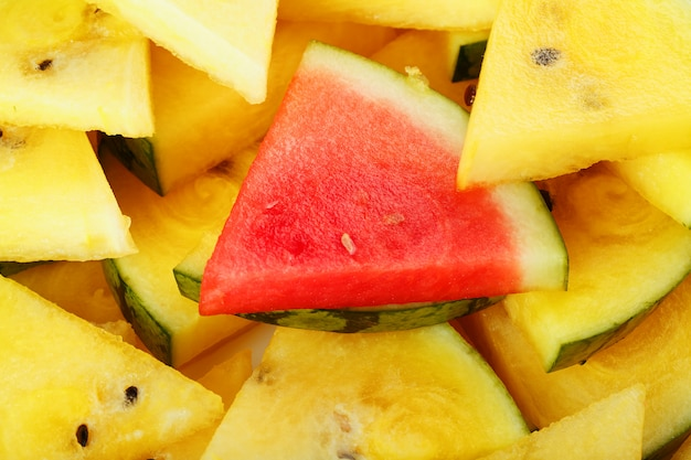 Pieces of red and yellow watermelon in a plate. a slice of red watermelon is one among the yellow pieces. highlight