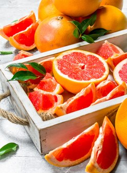 Pieces of ripe grapefruit on tray on white rustic table