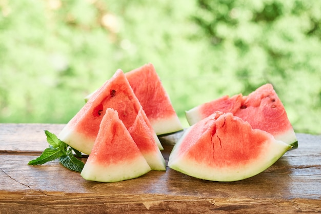 Pieces of ripe red watermelon are on a wooden plank, on green background of foliage. summer food, summer day, summer time