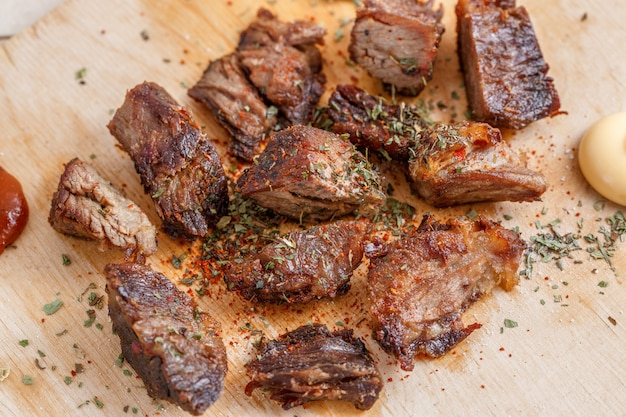 Pieces of roasted meat with spices on a wooden tray with four kinds of sauces to meat