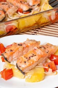 Pezzi di salmone con patate, pomodori e cipolle al forno