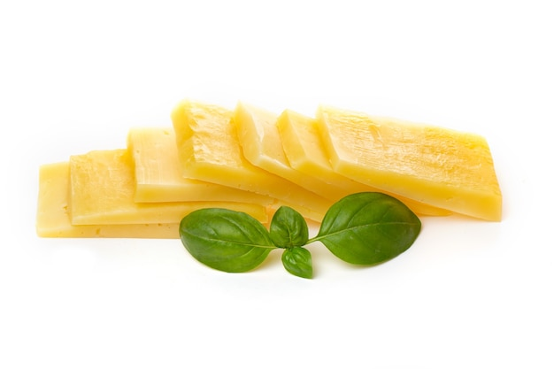 Pieces of semi-hard or hard yellow cheese with holes and basil leaf isolated on a white background.