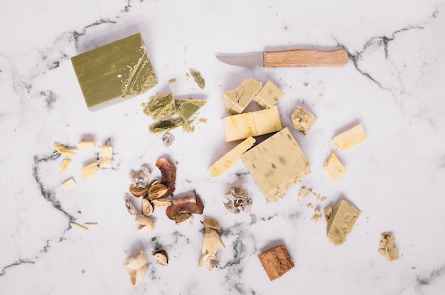 Pieces of soap bars and knife on marble backdrop