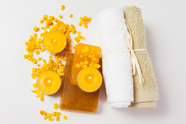 Pieces of soap, candles and towels on a white background