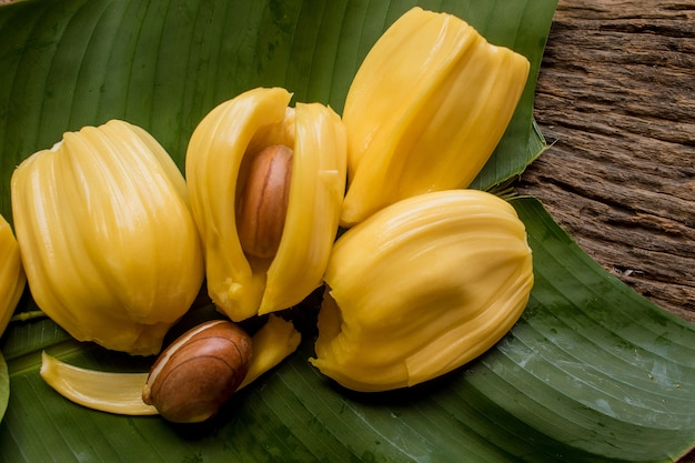 Pieces of sweet ripe jackfruit and seed laying on green banana leaf, tropical fruit.
