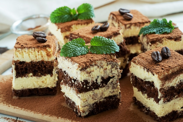 Pieces of tiramisu cake with delicate cream, coffee beans and mint leaves.