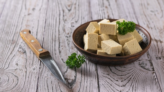 Pieces of tofu cheese in a clay bowl and a knife on a wooden table. soy cheese. vegetarian product.