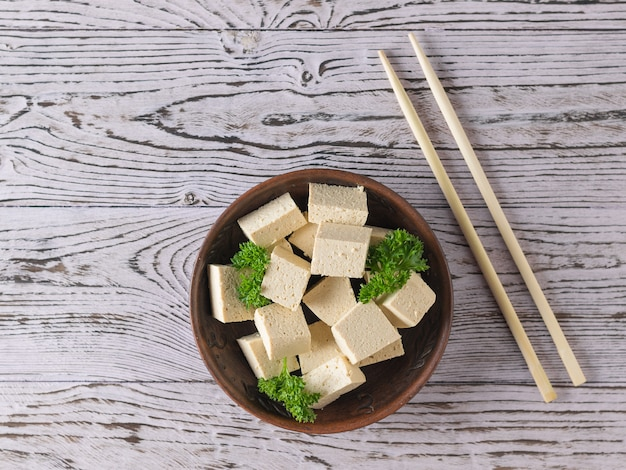Pieces of tofu cheese in a clay bowl and wooden sticks on a wooden table. soy cheese. vegetarian product. flat lay.