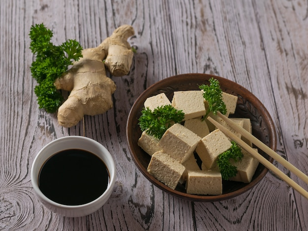 Pieces of tofu in a clay bowl and parsley leaves on a wooden table. soy cheese. vegetarian product.