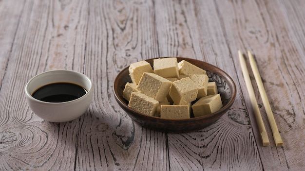 Pieces of tofu in a clay bowl, sauce and wooden sticks on a wooden table. soy cheese. vegetarian product.