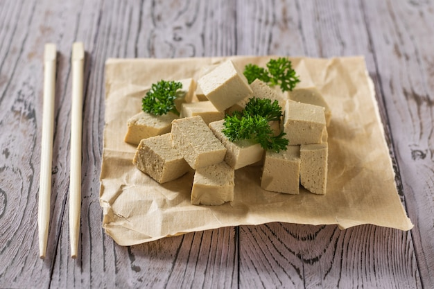 Pieces of tofu with greens on paper and chopsticks. soy cheese. vegetarian product.