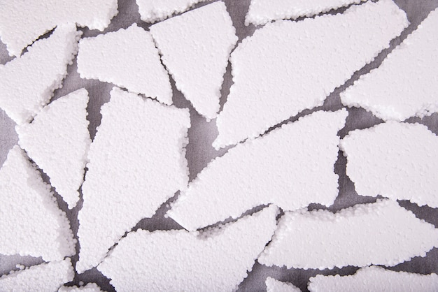 Pieces of white expanded polystyrene close-up on a gray background, flat layout.