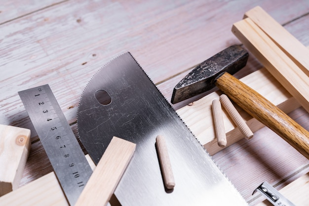 Pieces of wood and tools for construction and repair on a wooden table