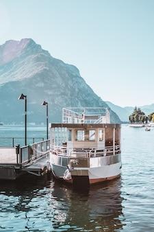 이탈리아 아름다운 산 풍경의 부두와 보트 코모 호수 해안