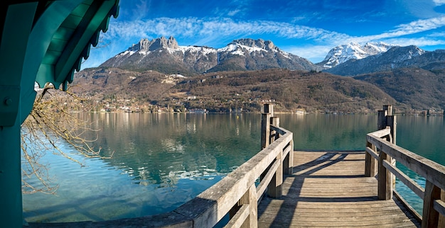 Pier in annecy with mountains in the background in the french alps