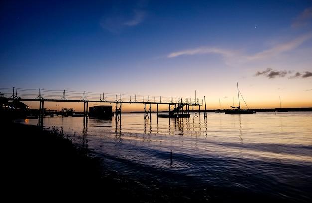 2004年4月3日、ジョアンペソアパライバブラジル近くのジャカレビーチカベデロの日没時の桟橋