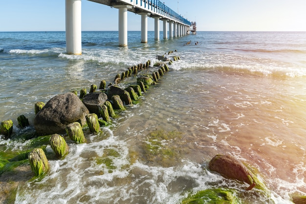 Pier on coast. surf waves with sea foam and seaweed on tourist beach. beautiful coast in sunlight. day seascape.