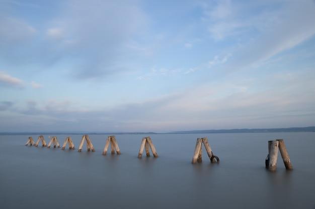 昼間の美しい曇り空の下の海の桟橋