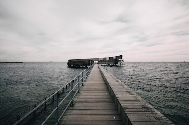 Pier leading to the ocean under the gloomy sky