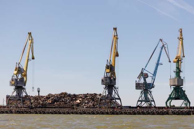 On the pier lies a large pile of metal scrap intended for loading into the vessel by using cranes